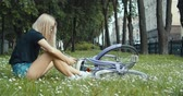blogger : Beautiful young woman sitting on grass and using phone on vintage bicycle background in summer park. 4K slow motion video footage 60 fps Stock Footage