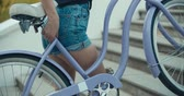 bisiklete binme : Woman cyclist walking up stairs and holding bicycle in arms. Woman bike city. 4K slow motion video footage 60 fps