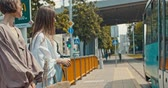 tram : Group of young women waiting the tram. Stylish girls waiting for the public transport while at the modern station outdoors. 4K slow motion raw video footage 60 fps Stock Footage