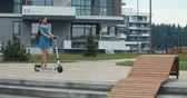 батарея : Attractive woman riding on the electric kick scooter. 4K slow motion video footage 60 fps Стоковые видеозаписи