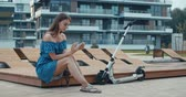 electric scooters : Woman sitting on bench among urban space and reading ebook using digital reader. Attractive girl with electric kick scooter. 4K slow motion raw video footage 60 fps Stock Footage