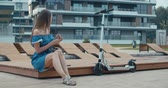 lambreta : Woman sitting on bench among urban space and reading ebook using digital reader. Attractive girl with electric kick scooter waiting friend . 4K slow motion raw video footage 60 fps Vídeos
