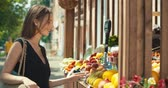 bolsa de compras : Woman choosing fruits in street kiosk in tourist city center. Girl buying fruits and vegetables at farmers shop. Healthy Food. 4K slow motion raw video footage 60 fps Stock Footage