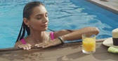 bronzlaşmış : Woman swims to the edge of swimming pool, takes fresh juice, drinks it and swims away, sunny day in the swimming pool outdoors, relaxing in the pool, 4k raw slow motion video footage