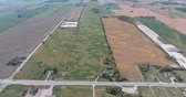 arazi sahibi : Aerial of Farm Fields While Descending Near Long Rows Of Corn Fields Stok Video
