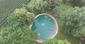 pó : Luxury Clear Blue Pond With Fountain In Center By Apple Orchard Aerial Flyover Vídeos