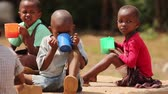 little : Young African children drinking from large plastic cups Stock Footage
