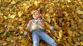 A little girl bathes in fallen autumn leaves.
