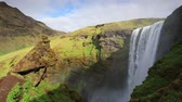 Colorful summer scene with flowing water of Skogafoss Waterfall, Iceland, Europe. Full HD video (High Definition).