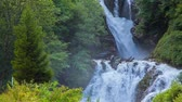 exploring : Beautiful waterfall shrouded fresh leaves near the Swiss village of Brunig. Alps, Switzerland, Europe. Stock Footage