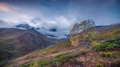 Time lapse clip. Flowing clouds around Ushba peak in autumn morning in the Caucasus mountains. Upper Svaneti, Georgia, Europe. 4K video (Ultra High Definition). Stock Footage