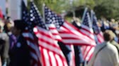 udatnost : American Flag bearers in soft focus