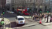 tornar : LONDON - MAY 2015: Red double decker bus in the city street, May 2015 London.This buses have become an icon of Britain and are a major tourist attraction in Themselves Stock Footage