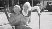 monocromático : Monochromatic view of elder couple using tablet outdoors with light rays Vídeos
