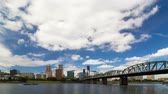 willamette : Ultra high definition 4k time lapse video of moving white clouds and blue sky over downtown skyline of Portland Oregon along Willamette River with Hawthorne bridge auto traffic in daylight 4096x2304 Stock Footage