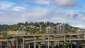 Time lapse movie of white clouds and blue sky over freeway traffic on Marquam bridge with residential homes and condominiums on hillside in downtown Portland Oregon 4k UHD 4096x2304