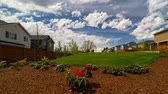 Time lapse 4k movie of moving white clouds and blue sky over luxury homes and beautiful green lawn landscaping in Happy Valley Oregon one sunny spring day uhd