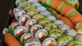 авокадо : High definition video zooming out of a platter of delicious sushi rolls prepared with both raw and cooked ingredients 1080p HD