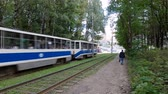 дорожный знак : Smolensk, RUSSIA - July 30, 2019: KTM-23 model tram with passengers is traveling along the city street. A pedestrian goes towards the tram next to the rails