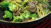 asian beef and broccoli stir fry with zucchini noodle cooking high heat on the pan closeup real time with audio