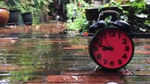 Slow motion clock on a garden floor in rainy days