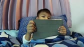cama : Asian kid playing game on tablet before going to sleep