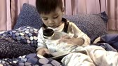 Asian boy in pyjamas is listening to music on his headphone. Japanese boy is using his tablet on his bed for music. Wideo