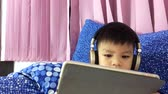 Asian boy is wearing headphone and watching cartoon on tablet. Japanese boy is using a tablet before bed time. Wideo