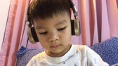 Japanese boy is putting his headphone to listen to Music in Bedroom. Asian boy is listening to Music with a headphone on his bed.
