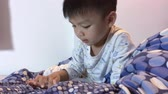 uyku : Asian boy is playing game on his tablet in the bed. Japanese boy is using a tablet before bed time. Stok Video