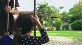 Grand parent helping her grand children to play on the swing in a garden.