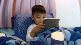 Asian kid playing game on tablet before going to sleep
