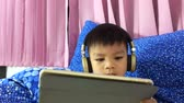 relaxation : Asian child is wearing a headphone and watching cartoon on his tablet.