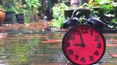 clock : Time lapse of a red alarm Clock speeding up on rainy day