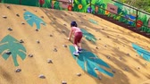 挑戦 : Little girl is climbing up a rock wall in playground