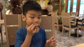 little boy eating friend chicken wing in a cafe