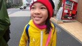 radość : Tokyo, Japan - March 23, 2019: Little tourist girl is laughing in the street of Tokyo.