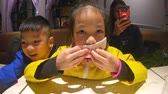 A girl wiping her mouth with wet tissue napkin in restaurant Vídeos