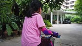 Little girl is learning to ride a bike in backyard Vídeos
