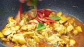 bazylia : put sweet basil , bell pepper into the black pan which stir fried chicken , sliced corn and long yard beans,  spices , curry paste and  food palm oil  in the pan
