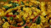 çili : zoom out of  stir fried chicken with spicy curry paste , sweet basil, bell pepper, long yard beans , sliced corn in blue dish