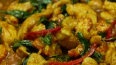çili : panning of  fried chicken with spicy curry paste , sweet basil, bell pepper, long yard beans , sliced corn in blue dish