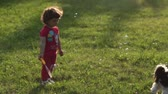 pleasantly : Little curly girl walking with her grandmother and dog and blow bubbles