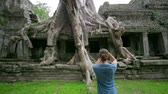 снимок : visitor taking picture bizarre nature of preah khan temple, angkor Стоковые видеозаписи