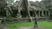 bizarro : Happy man raising arms in mysterious preah khan temple, angkor Stock Footage