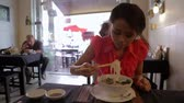 chop sticks : Asian girl eating noodle in a local restaurant, phnom penh Stock Footage