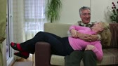 couch : Senior couple laughing and talking while sitting on sofa Stock Footage