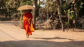 careca : SILK ISLAND, CAMBODIA - MARCH 2014: buddhist monk walking on countryside holding umbrella