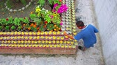 offers : KATHMANDU, NEPAL - JUNE 2013: Man pouring water at pot flowers at the holy site of Boudhanath, Kathmandu, Nepal