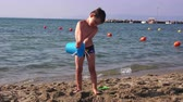 kazma : Little boy on a sea beach playing in the sand Stok Video